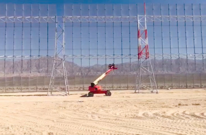 Workers in a 'cherry-picker' lend a sense of scale to the smart fence being installed around the country's newest civilian airport currently under construction (photo credit: DEFENSE MINISTRY)
