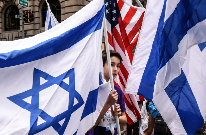 A boy is surrounded by Israeli and American flags (photo credit: REUTERS/STEPHANIE KEITH)