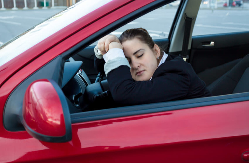 A woman asleep in the driver's seat of her car (photo credit: INGIMAGE)