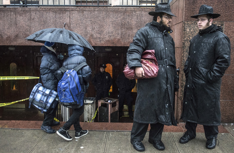 Policemen (background) keep guard as men and boys stand at a Brooklyn synagogue in New York City. (photo credit: REUTERS)