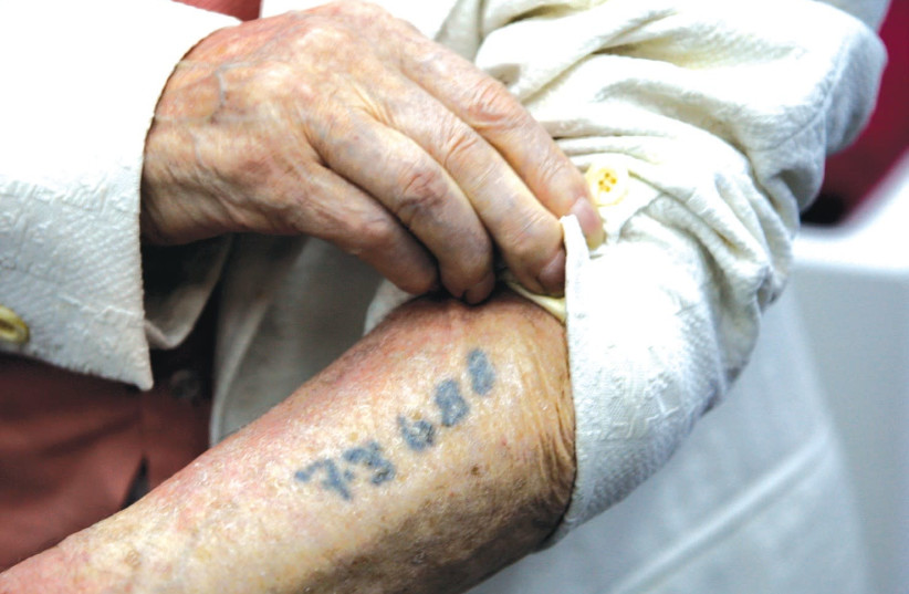 A Holocaust survivor shows the number that was tattooed on his arm in a Nazi concentration camp during the Holocaust (photo credit: BAZ RATNER/REUTERS)