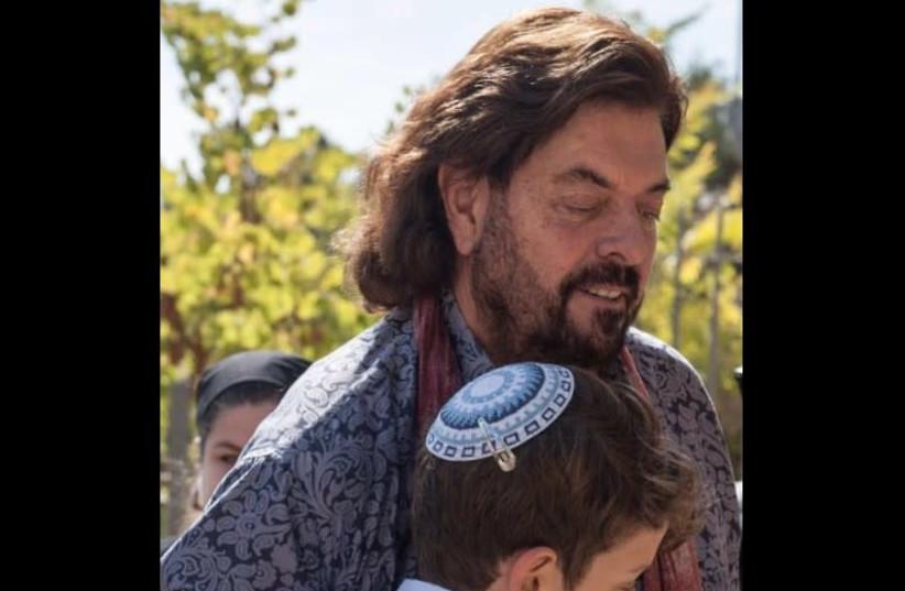Alan Parsons embraces 13-year-old Tal Erez outside the Yemin Moshe synagogue this week at his bar mitzva (photo credit: MICHAEL SHVADRON)