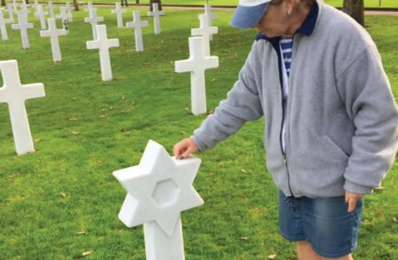 A VISITOR to the American military cemetery in Normandy places a stone on the grave of one of the 300 Jewish soldiers interred there. (photo credit: STEWART WEISS)