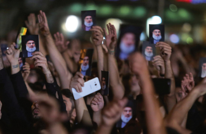 LEBANON'S HEZBOLLAH supporters hold photographs of leader Hassan Nasrallah during his address via a video screen in Beirut last September.  (photo credit: KHALIL HARAN / REUTERS)