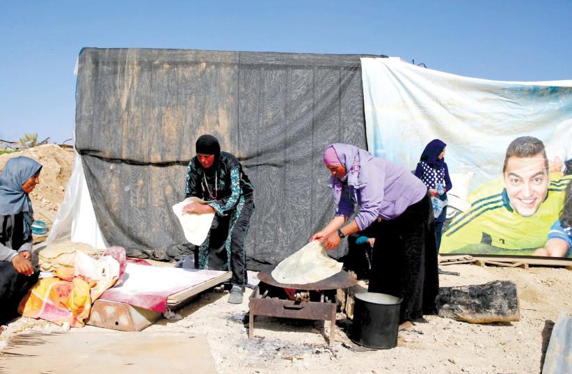Women prepare traditional flat bread in the Beduin village of Umm al-Hiran, northeast of Beersheba. (photo credit: AMMAR AWAD/REUTERS)