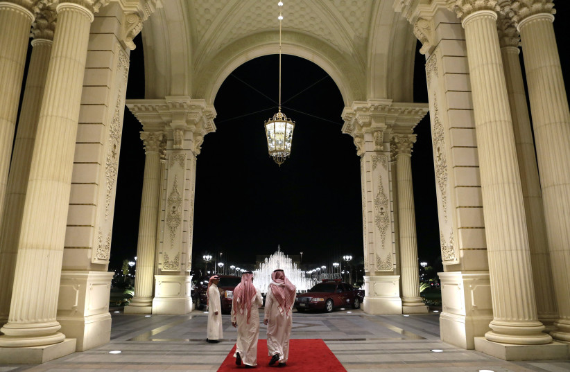 Saudi men walk at the entrance to the Ritz-Carlton Hotel. (photo credit: REUTERS)