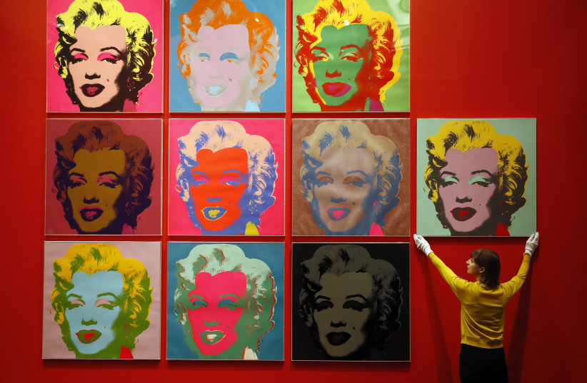 An employee poses with ten screenprints of Marilyn Monroe by Andy Warhol (photo credit: REUTERS)