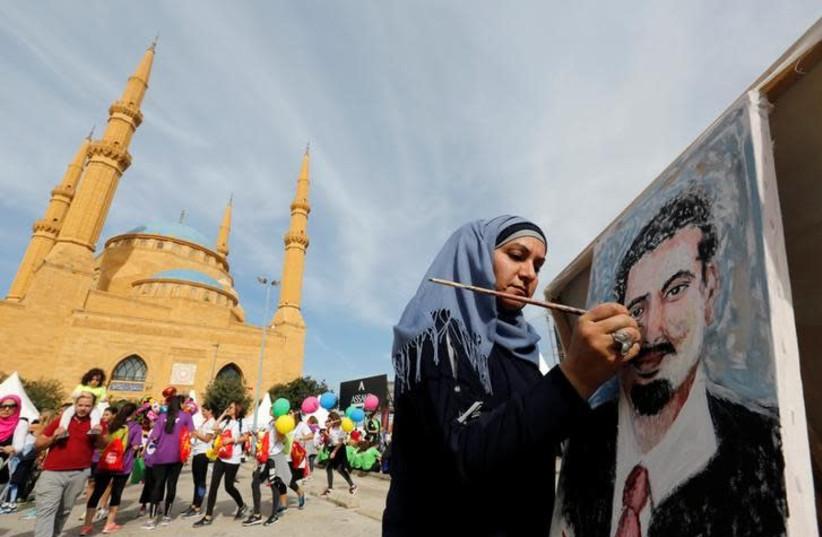 Youmn Ahmad, a Lebanese artist, paints a portrait of Lebanon's Prime Minister Saad al-Hariri, who has resigned from his post, during the annual Beirut Marathon, in Beirut Lebanon November 12, 2017 (photo credit: REUTERS/JAMAL SAIDI)