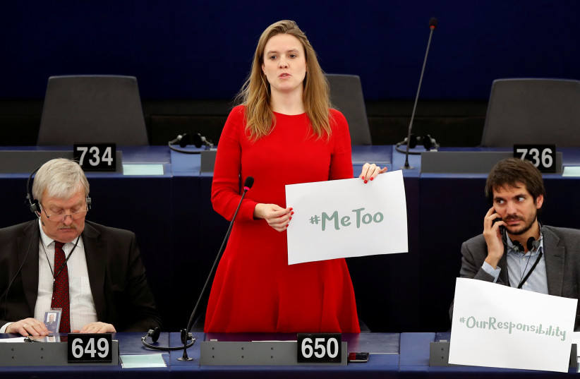 """European Parliament member Terry Reintke (C) holds a placard with the hashtag """"MeToo"""" during a debate to discuss preventive measures against sexual harassment and abuse in the EU at the European Parliament in Strasbourg, France, October 25, 2017. (photo credit: REUTERS/CHRISTIAN HARTMANN)"""