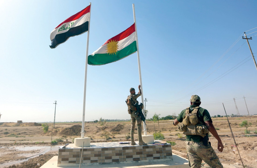 A MEMBER of the Iraqi security forces takes down a Kurdish flag in Kirkuk, Iraq. (photo credit: REUTERS)