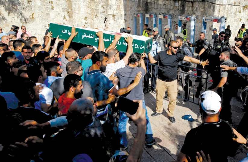 MUSLIMS ARGUE with Border Police officers as they carry a coffin at an entrance to the Temple Mount on July 16, wishing to hold a funeral inside the Aksa Mosque. (photo credit: AMMAR AWAD / REUTERS)