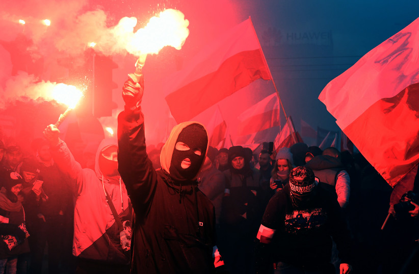 Demonstrators burn flares and wave Polish flags during the annual march to commemorate Poland's National Independence Day in Warsaw (photo credit: AFP PHOTO / JANEK SKARZYNSKI)
