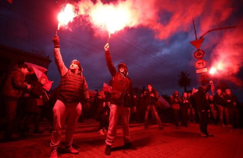 Protesters light flares and carry Polish flags during a rally, organised by far-right, nationalist groups, to mark 99th anniversary of Polish independence in Warsaw, Poland November 11, 2017 (photo credit: AGENCJA GAZETA/ADAM STEPIEN VIA REUTERS)