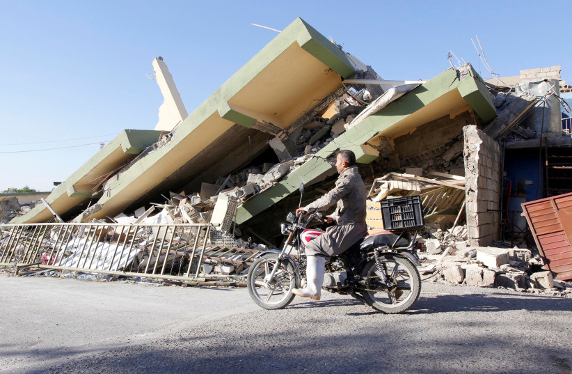 A man rides past the remains of a building in Darbandikhanm, Kurdistan, after a 7.2 magnitude earthquake there, November 2017 (photo credit: AKO RASHEED / REUTERS)