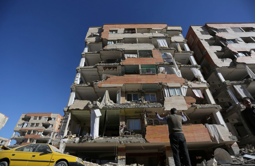 A man reacts as he looks at a damaged building following an earthquake in Iran (photo credit: REUTERS/TASNIM NEWS AGENCY)