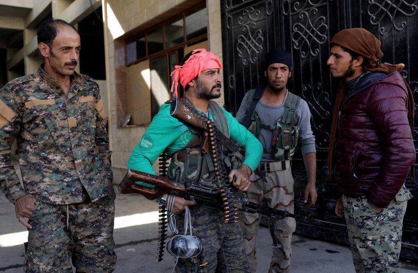 Fighters from the Syrian Democratic Forces (SDF) stand together in Raqqa, Syria, October 16, 2017.  (photo credit: REUTERS)