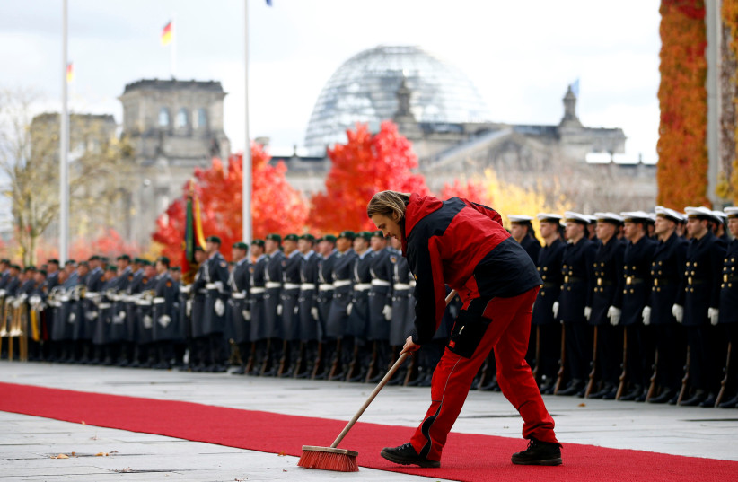 An employee of the chancellery sweeps the red carpet in front of the honour guard before a welcoming ceremony at the chancellery in Berlin, Germany November 2, 2016.  (photo credit: REUTERS)