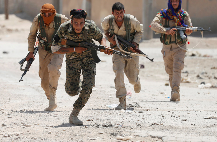 Kurdish fighters from the People's Protection Units (YPG) run across a street in Raqqa, Syria  (photo credit: REUTERS/GORAN TOMASEVIC/FILE PHOTO)