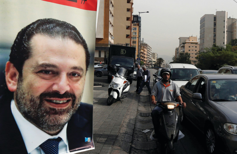 CARS PASS next to a poster depicting Saad Hariri in Beirut earlier this week. Hariri resigned as Lebanon's prime minister on November 4 (photo credit: REUTERS/MOHAMED AZAKIR)