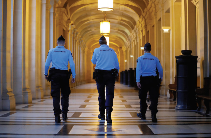 FRENCH GENDARMES walk in the corridors of a Paris courthouse before the verdict in the trial of Abdelkader Merah, brother of gunman Islamist militant Mohammed Merah, who killed 7 people in 2012. (photo credit: REUTERS)