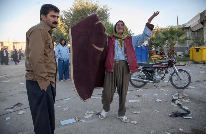 A man reacts following an earthquake in Sarpol-e Zahab county in Kermanshah, Iran (photo credit: TASNIM NEWS AGENCY/HANDOUT VIA REUTERS)