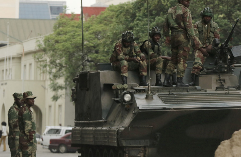 Soldiers are seen next to and on the armoured vehicle on the street in central Harare, Zimbabwe, November 16, 2017. (photo credit: REUTERS)