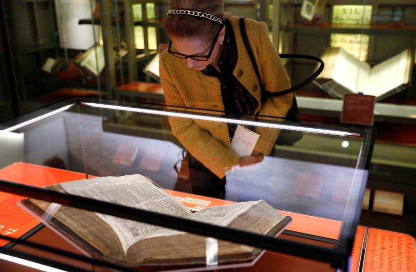 A woman looks at a Bible during a preview of the Museum of the Bible in Washington, U.S., November 14, 2017 (photo credit: KEVIN LAMARQUE/REUTERS)