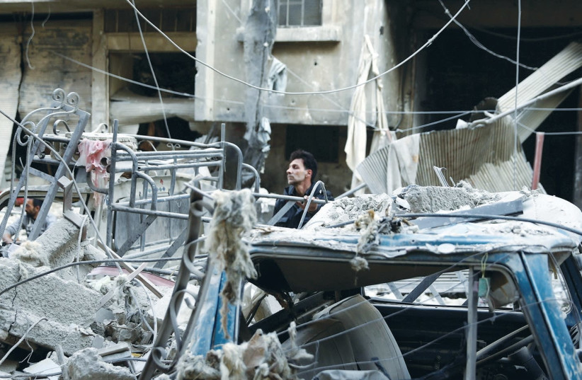 SYRIAN RESIDENTS react to a shelling in the eastern Damascus suburb of Ghouta on Friday (photo credit: REUTERS)