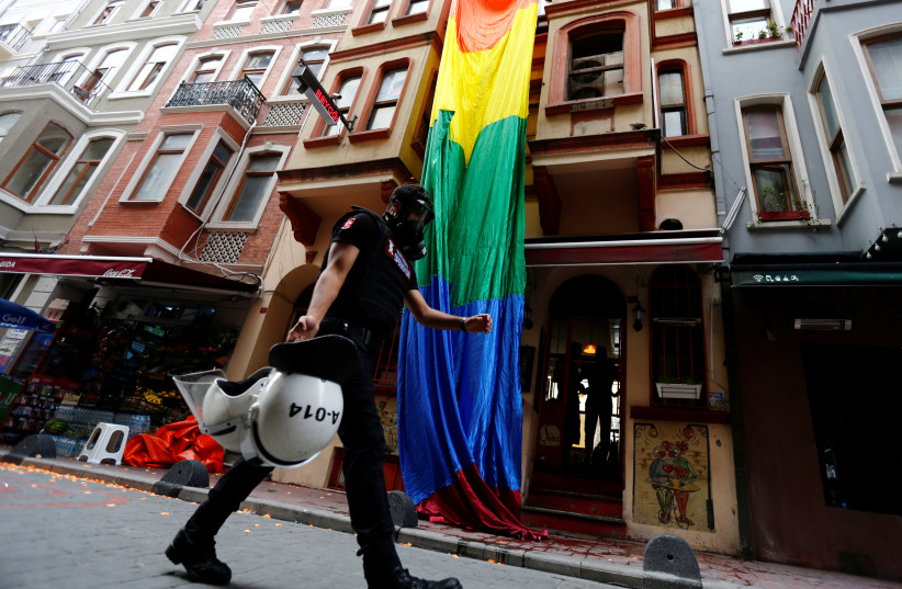 A riot police, with a rainbow flag in the background, chases LGBT rights activists as they try to gather for a pride parade, which was banned by the governorship, in Istanbul, Turkey (photo credit: REUTERS/MURAD SEZER)