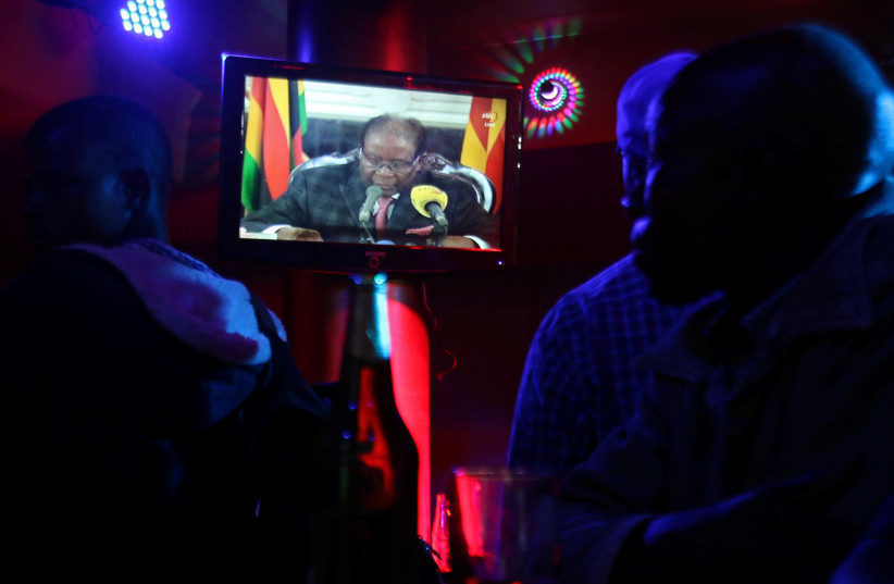 People watch as Zimbabwean President Robert Mugabe addresses the nation on television, at a bar in Harare, Zimbabwe, November 19, 2017 (photo credit: REUTERS/PHILIMON BULAWAYO)