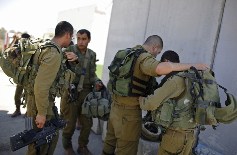 Israeli soldiers wear their combat gear near a shelter at Kerem Shalom crossing August 1, 2014. (photo credit: AMIR COHEN - REUTERS)