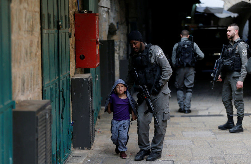An Israeli border policeman escorts a boy away from a blocked alley in Jerusalem (photo credit: AMMAR AWAD / REUTERS)