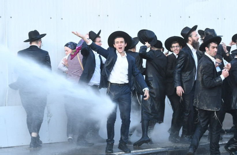 Ultra-Orthodox protestors of the draft are sprayed with water canons in Bnei Brak (photo credit: AVRAHAM SASSONI)