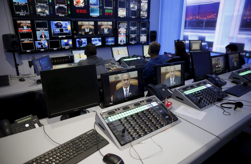 Prime Minister Benjamin Netanyahu is seen on monitors in Channel 10's control room (photo credit: RONEN ZVULUN / REUTERS)