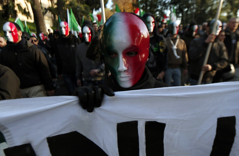 A member of Casapound far-right organization wears a mask in the colours of the Italian flag before a demonstration in Rome (photo credit: YARA NARDI / REUTERS)