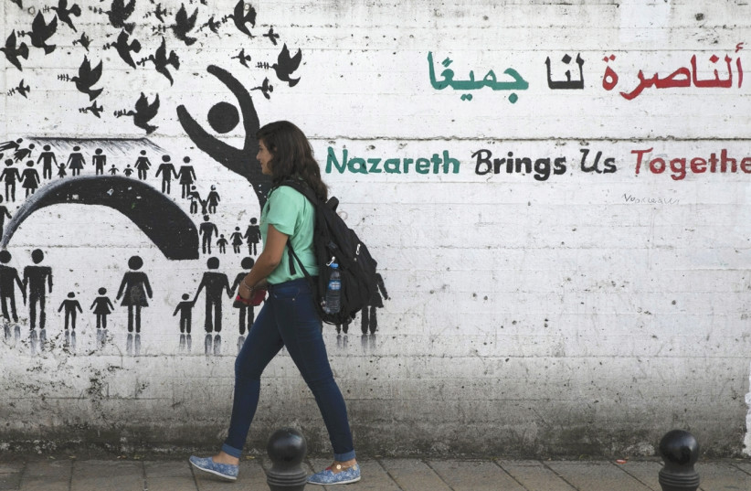 A YOUTH walks past graffiti on a street in Nazareth. (photo credit: REUTERS)