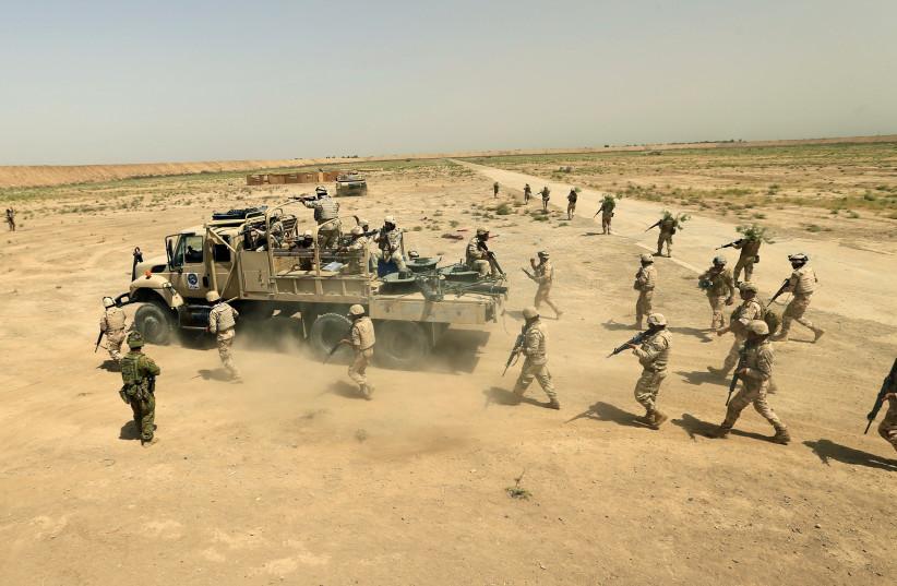 Iraqi army members participate in a live ammunition training exercise with coalition forces trainers at Taji base in August 2017 (photo credit: REUTERS)