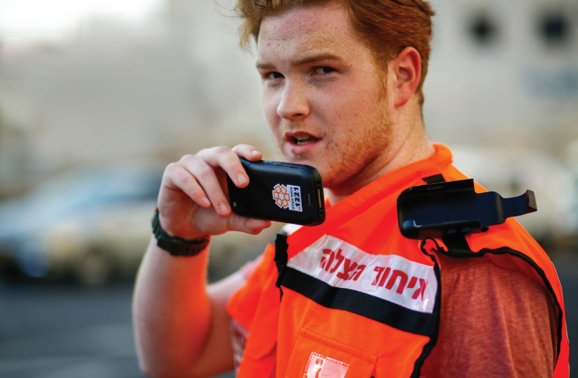A UNITED HATZALAH volunteer holds the new smartphone mobile device that will be issued to all of the organization's volunteers. (photo credit: COURTESY UNITED HATZALAH)