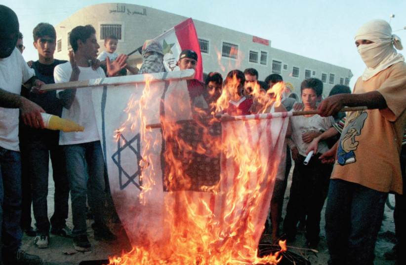 PALESTINIAN DEMONSTRATORS burn American and Israeli flags on the top of a symbolic coffin with the words 'Oslo accords' written on it in September 1993. (Reuters) (photo credit: REUTERS)