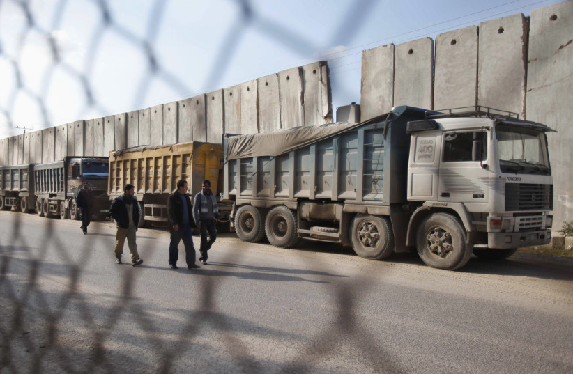 Palestinians walk past trucks loaded with gravel at the Kerem Shalom crossing between Israel and the southern Gaza Strip December 30, 2012. (photo credit: REUTERS)