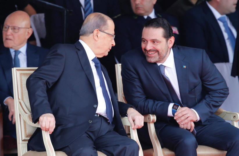 Saad al-Hariri talks with Lebanese President Michel Aoun while attending a Lebanese Independence Day military parade (photo credit: MOHAMED AZAKIR / REUTERS)