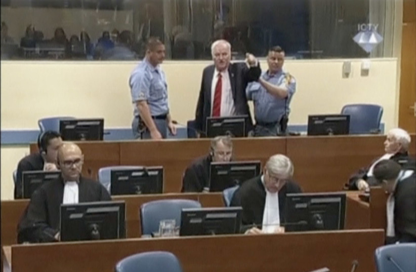 Ex-Bosnian Serb wartime general Ratko Mladic reacts in court at the International Criminal Tribunal for the former Yugoslavia (ICTY) in the Hague, Netherlands in this still image taken from a video released by the International Criminal Tribunal for the former Yugoslavia (ICTY), November 22, 2017 (photo credit: REUTERS)