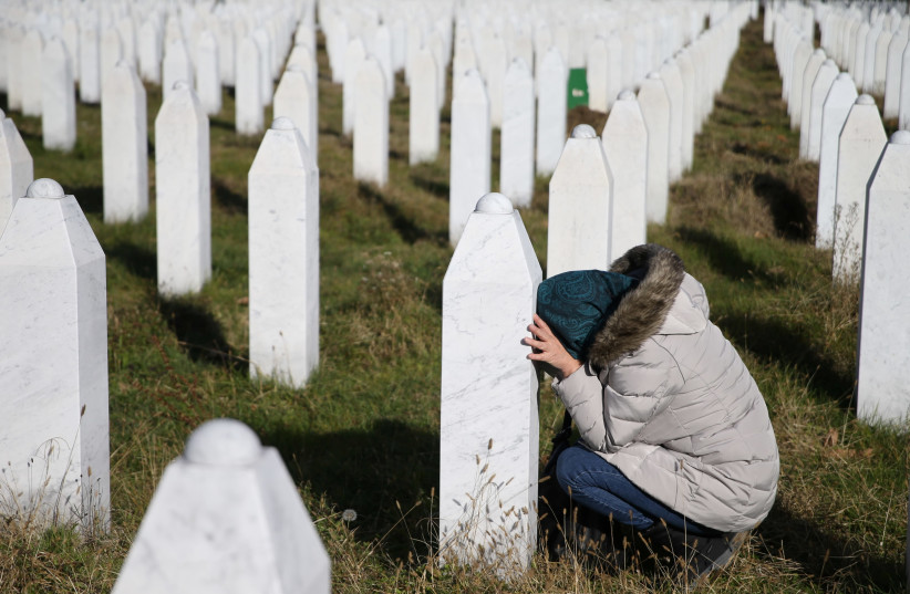 A woman reacts near a grave of her family members in the Memorial centre Potocari near Srebrenica, Bosnia and Herzegovina, after the court proceedings of former Bosnian Serb general Ratko Mladic, November 22, 2017 (photo credit: REUTERS/ DADO RUVIC)