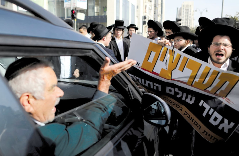 A DRIVER argues with haredi men as they protest against the detention of members of their community who failed to report to a military recruiting office, in Jerusalem last month. The placard in Hebrew reads, 'Fans of those imprisoned from the Torah world.' ( (photo credit: AMMAR AWAD / REUTERS)