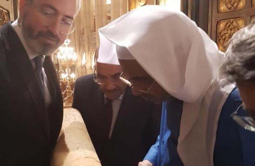 Rabbi Moshe Sebbag shows a Torah scroll to Secretary General of the Muslim World League Dr. Muhammad Abdul-Kareem al-Issa and Khalid bin Mohammed Al Angari, Saudi Arabia's ambassador to France, during thier visit to the Great Synagogue of Paris this week.  (photo credit: Courtesy)