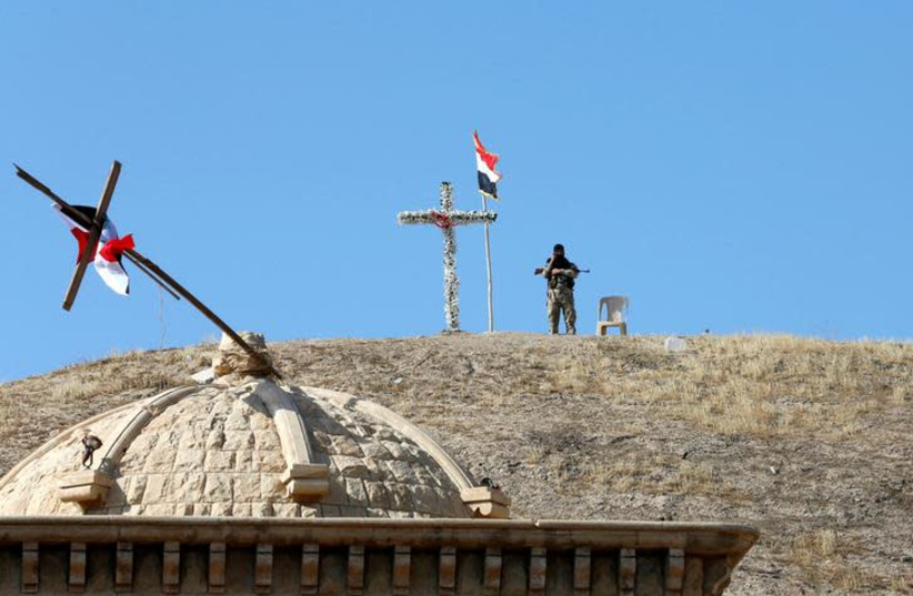 An Iraqi Christian soldier guards the church of Saint Barbara after it was recaptured from Islamic State, near Mosul (photo credit: AHMED JADALLAH / REUTERS)