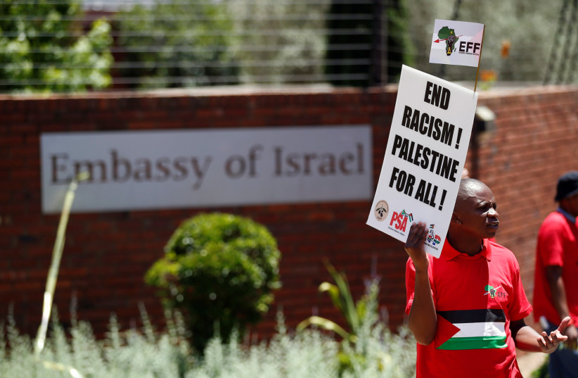A protester and member of South Africa's ultra-left Economic Freedom Fighters party (EFF), carries a placard outside the Israeli embassy in Pretoria, South Africa (photo credit: SIPHIWE SIBEKO/REUTERS)
