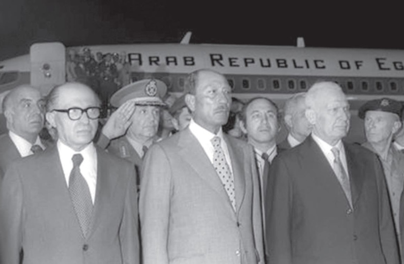 Egyptian President Anwar Sadat and Israeli Prime Minister Menachem Begin stand together at Ben Gurion Airport after Sadat's arrival on November 19, 1977. (photo credit: GPO)
