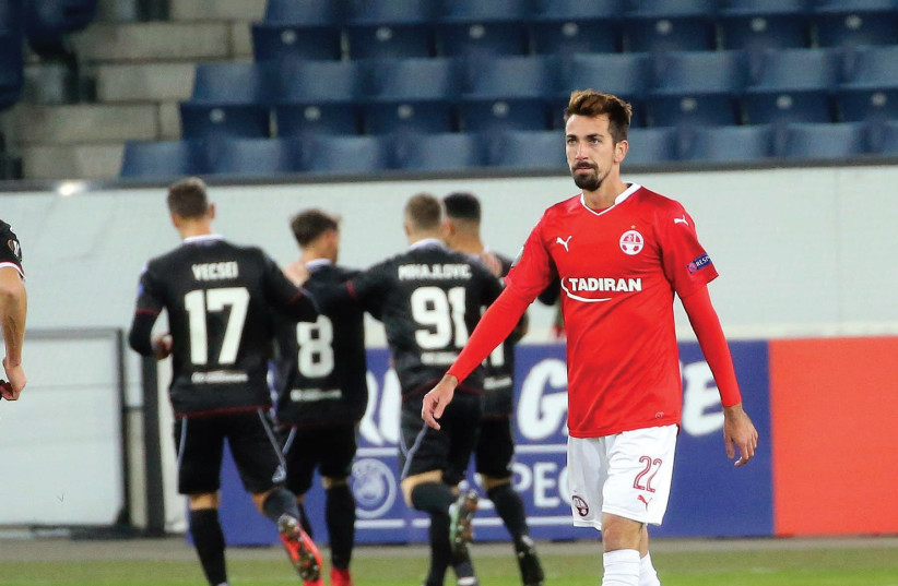 Hapoel Beersheba midfielder Isaac Cuenca walks away disappointed while Lugano players celebrate scoring their winner in the background in a 1-0 victory in Europa League action in Switzerland. (photo credit: UDI ZITIAT)