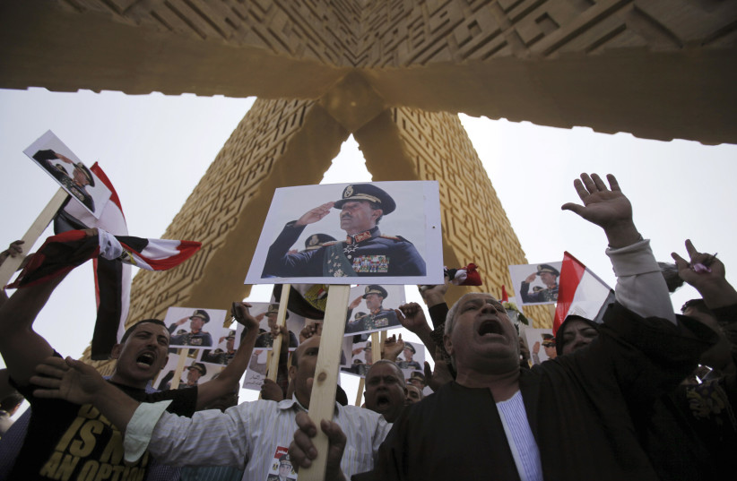 Supporters of the army hold posters of Egyptian president Anwar Sadat at his tomb in Cairo. (photo credit: REUTERS)